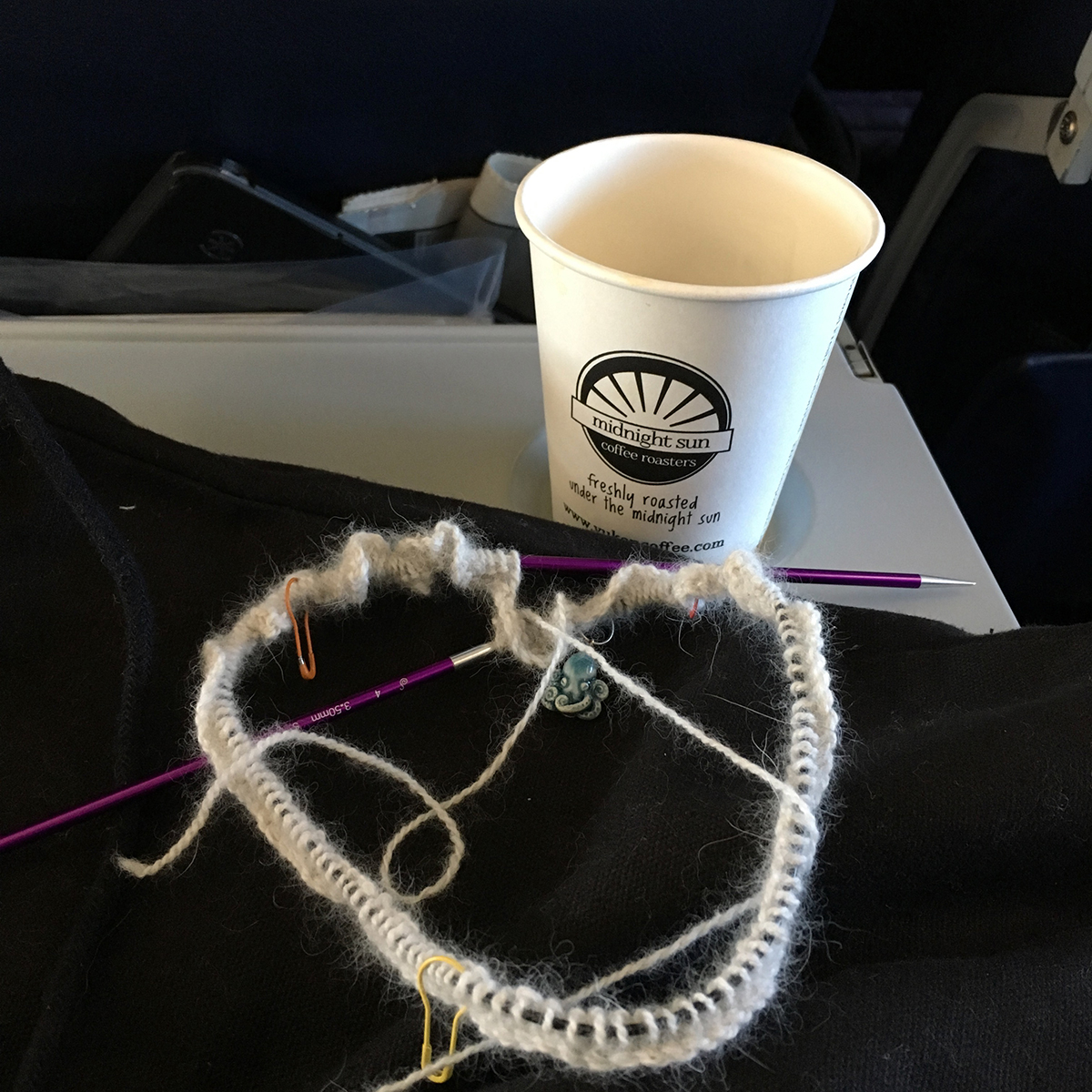 A round of knitting, just cast on, and an empty coffee cup on an airplane seat back table. A tablet sticks out from the seat back pocket in back of the photo.