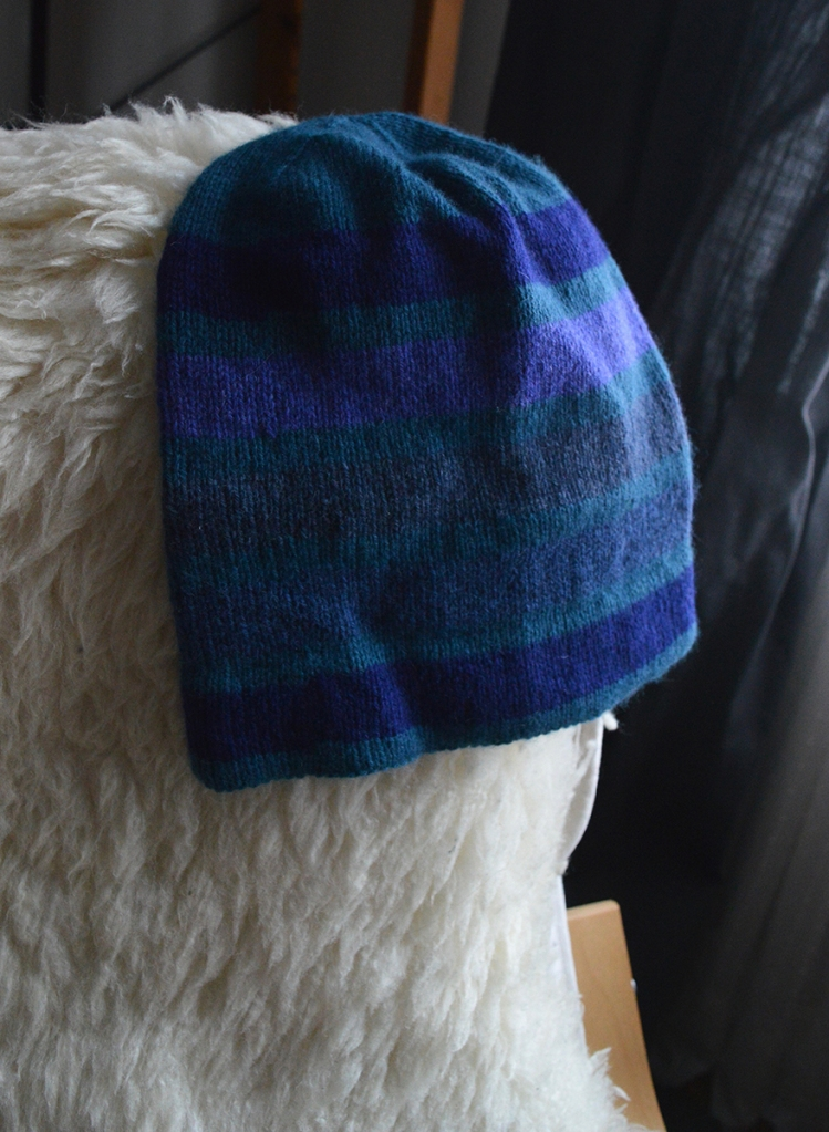 A handknit hat draped over the back of a chair. The hat is worked in stripes of teal and blue, with one stripe in a sort of bluish purple.
