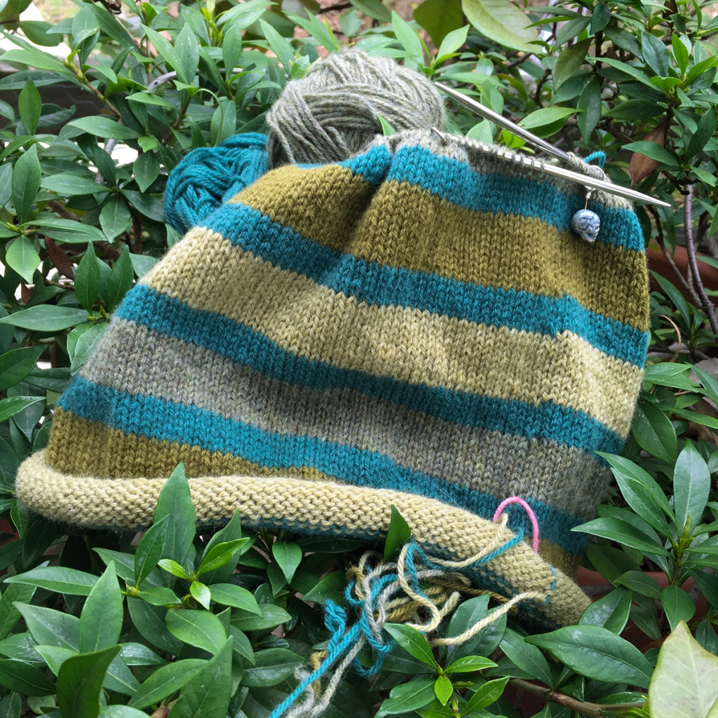 A handknit stripey hat in progress, worked in teal, gold, pale yellow-green, and pale greyish-green.