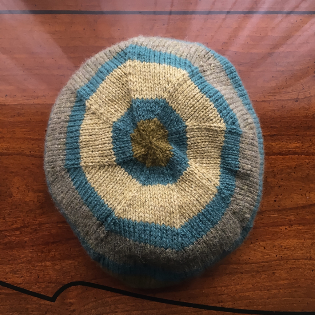 The crown of a striped, handknit hat.