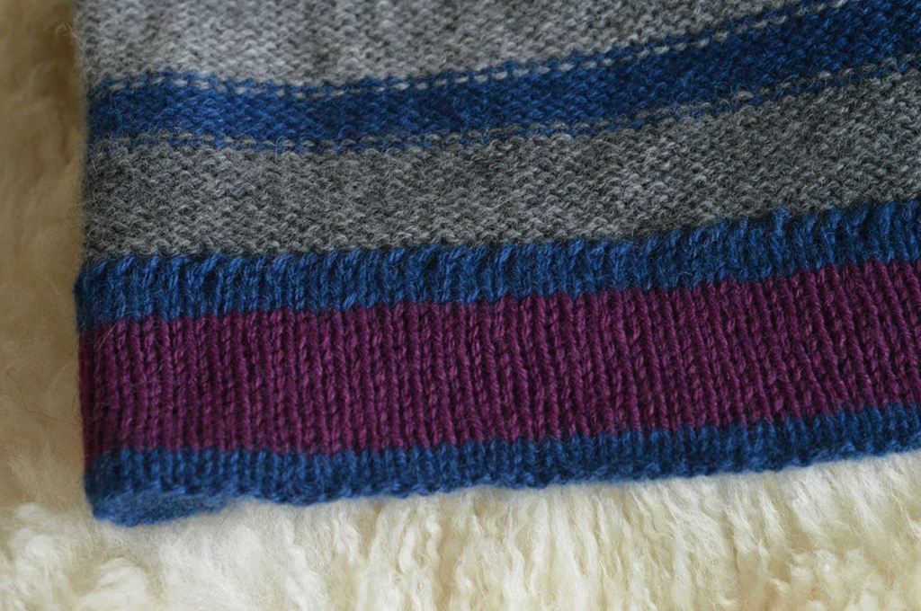 Close up of the hem of a stripey hat, showing the stitching that secures the hem.