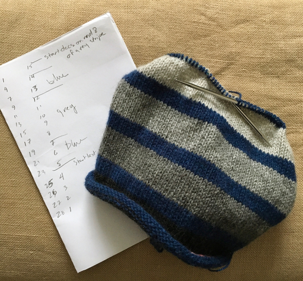 A blue and grey stripey hat in progress, with the crown decrease striping worked out in pencil beside it.