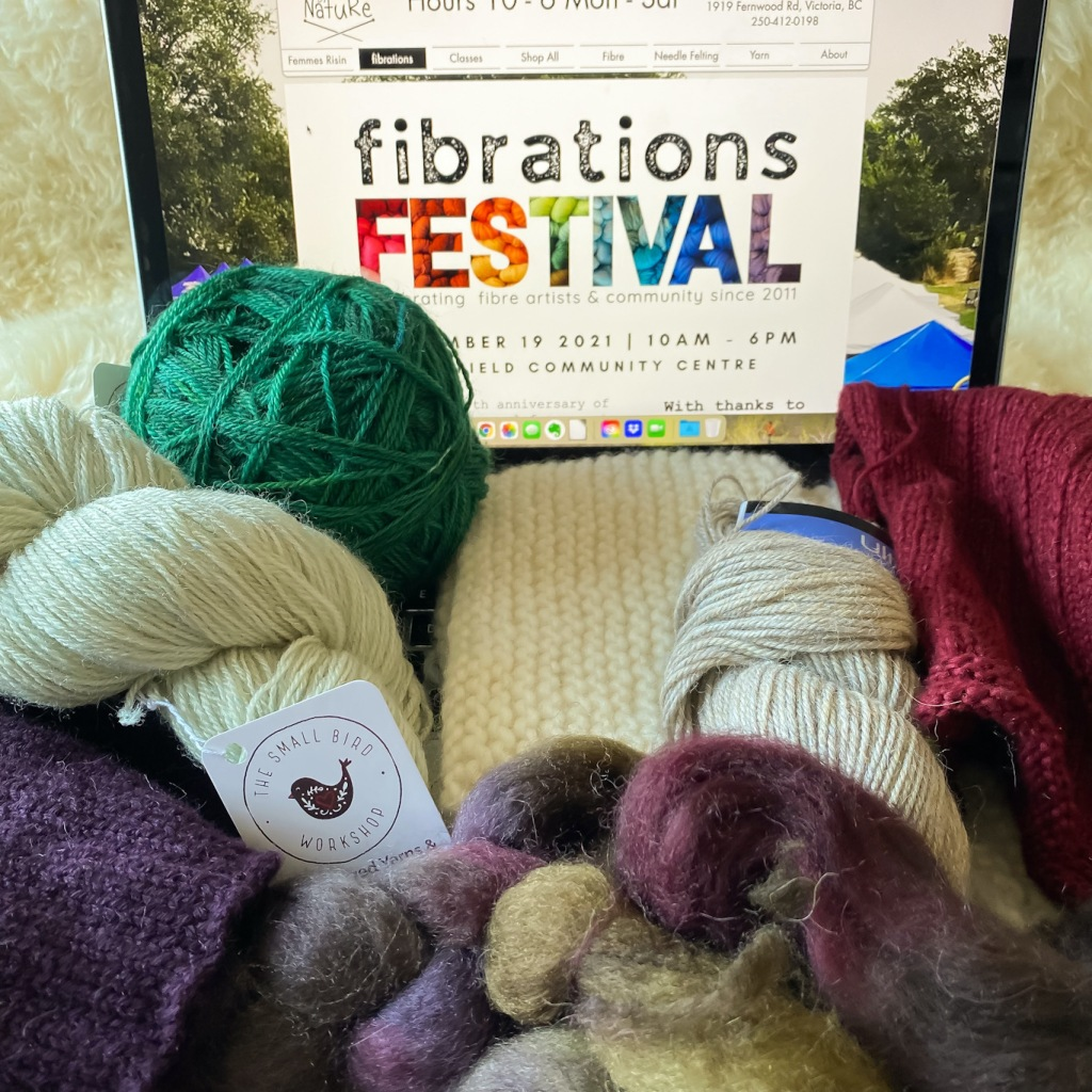 Yarn, spinning fibre, and knitting projects in progress, sitting in front of a computer screen with the splash page of Fibrations Festival showing on it.